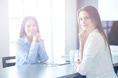 2 женских коллеги в офисе сидя на столе Стоковые Изображения