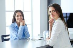 2 женских коллеги в офисе сидя на столе Стоковая Фотография RF