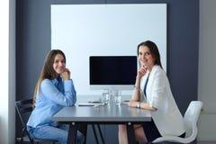 2 женских коллеги в офисе сидя на столе Стоковое Фото