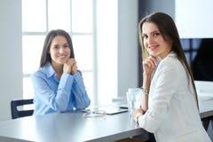2 женских коллеги в офисе сидя на столе Стоковое Изображение