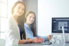 2 женских коллеги в офисе сидя на столе Стоковое Изображение RF