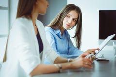2 женских коллеги в офисе сидя на столе Стоковая Фотография