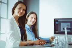 2 женских коллеги в офисе сидя на столе Стоковые Фото