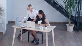 2 женских коллеги говоря в офисе Стоковое фото RF