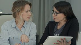 2 женских коллеги коллективно обсуждать в офисе используя таблетку Стоковые Изображения RF
