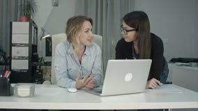 2 женских коллеги обсуждая новую идею проекта используя компьтер-книжку Стоковые Фото