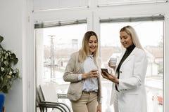 2 женских коллеги смотря мобильный телефон Стоковое фото RF