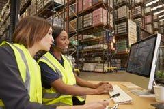 2 женских коллеги работая в офисе склада Стоковое фото RF