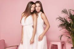 2 женских модели представляя в элегантных платьях Стоковое Фото