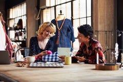 2 женских модельера в встрече обсуждая ткани Стоковые Фотографии RF