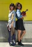 2 женских музыканта стоя спина к спине держащ аппаратуры Стоковые Изображения