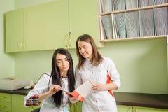 2 женских доктора в белой форме на офисе клиники зубоврачевание Стоковое фото RF