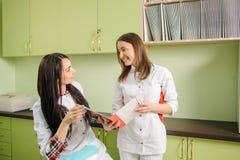 2 женских доктора в белой форме на офисе клиники зубоврачевание Стоковое Изображение RF