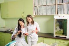 2 женских доктора в белой форме на офисе клиники зубоврачевание Стоковое Изображение