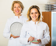 2 женских доктора держа часы Стоковые Фото