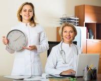 2 женских доктора держа часы Стоковое Фото