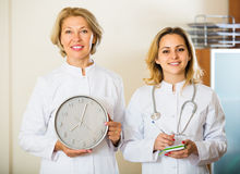 2 женских доктора держа часы Стоковые Изображения