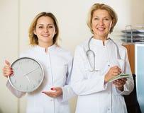 2 женских доктора показывая время в часах Стоковые Изображения RF