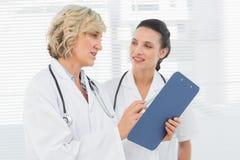 2 женских доктора читая медицинские заключения Стоковые Фотографии RF