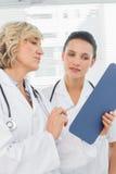 2 женских доктора читая медицинские заключения Стоковые Фото