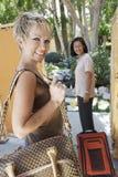 2 женских отдыхающего с багажом Стоковые Фотографии RF
