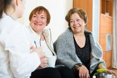 2 женских пенсионера обсуждая проблемы здоровья с доктором Стоковое Изображение RF