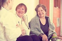 2 женских пенсионера обсуждая проблемы здоровья с доктором Стоковое Фото