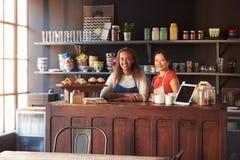 2 женских предпринимателя кофейни стоя за счетчиком Стоковое Фото