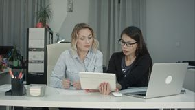 2 женских профессионала используя цифровую таблетку пока работающ на столе Стоковые Изображения