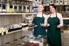 2 женских продавца нося рисберму Стоковая Фотография