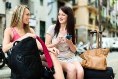 2 женских путешественника используя систему smartphone проводя Стоковое Изображение