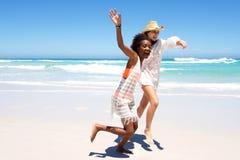 2 женских друз бежать на пляже совместно Стоковое фото RF