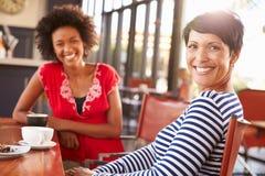 2 женских друз встречая на кофейне Стоковые Изображения