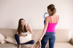 2 женских друз выбирая одежду для партии Стоковое Фото