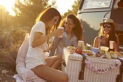 3 женских друз говоря на пикнике их жилым фургоном Стоковые Фото