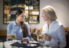 2 женских друз говоря на таблице и усмехаться кафа Стоковые Фотографии RF