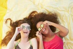 2 женских друз лежа на кровати используя косметики Стоковое фото RF