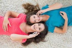 2 женских друз лежа на половике и используя мобильный телефон Стоковое Изображение