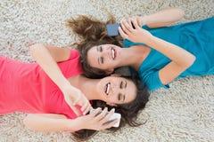 2 женских друз лежа на половике и обмене текстовыми сообщениями Стоковое фото RF