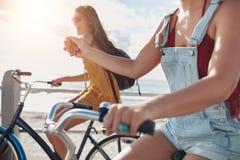 2 женских друз держа руки и ехать циклы Стоковые Изображения RF