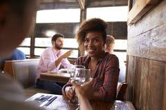 2 женских друз делая здравицу на таблице в баре Стоковая Фотография