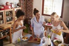 3 женских друз делая smoothies в кухне Стоковые Изображения