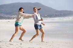 2 женских друз играя на пляже Стоковое фото RF