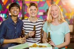 3 женских друз имея бутылку пива и пиццы в партии Стоковые Изображения