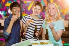 3 женских друз имея бутылку пива и пиццы в партии Стоковое Изображение RF