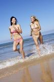 2 женских друз имея потеху на празднике пляжа совместно Стоковое Фото