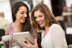 2 женских друз используя таблетку Стоковое Изображение