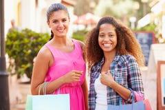 2 женских друз идя вдоль улицы с хозяйственными сумками Стоковое фото RF
