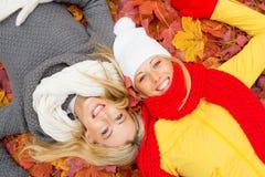 2 женских друз кладя в листья Стоковое Изображение