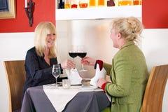 2 женских друз наслаждаются расслабляющим питьем Стоковые Фото